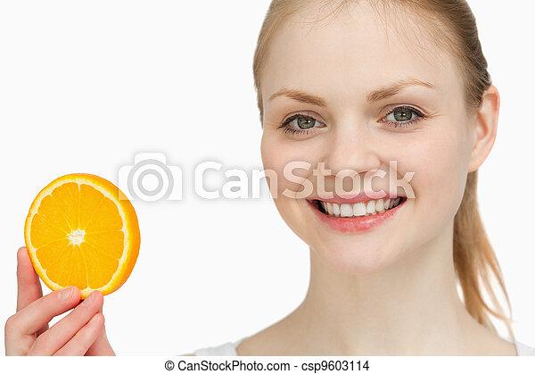 Smiling woman presenting an orange slice - csp9603114