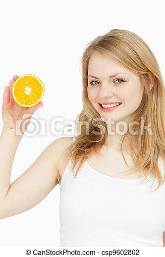 Smiling woman presenting an orange - csp9602802