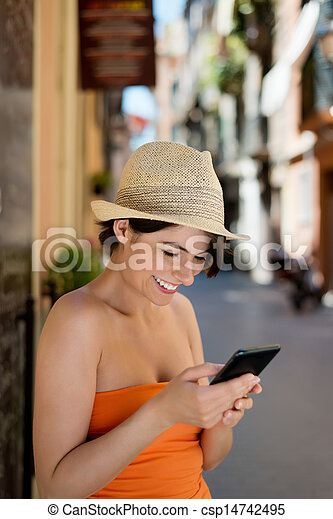 Smiling woman reading a sms on her mobile - csp14742495