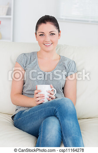Smiling woman sitting on the couch and holding a mug - csp11164278