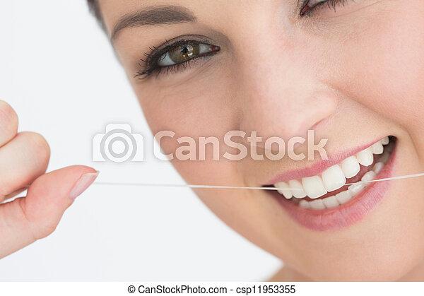 Smiling woman using dental floss - csp11953355