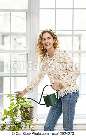 Smiling woman watering plant at home - csp12924273
