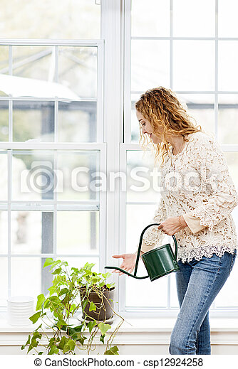 Smiling woman watering plant at home - csp12924258