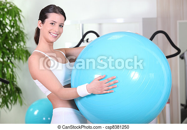 Smiling woman with an exercise ball in a gym - csp8381250