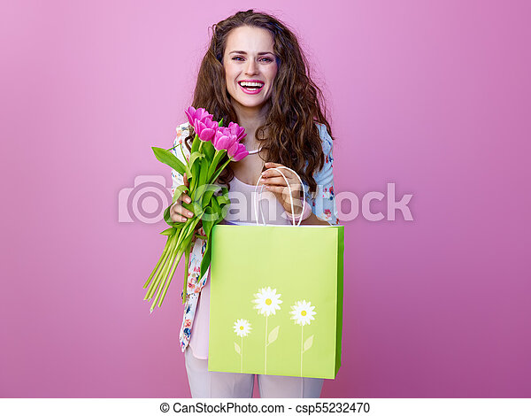 smiling woman with bouquet of flowers showing shopping bag - csp55232470