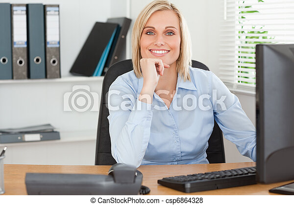 Smiling woman with chin on hand behind a desk - csp6864328