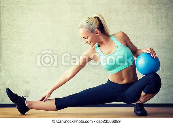 smiling woman with exercise ball in gym - csp23586899