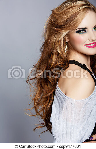 smiling woman with long curly hair and pink lipstick - csp9477801
