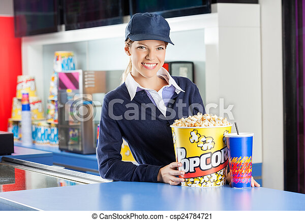 Smiling Worker With Snacks At Cinema Concession Counter - csp24784721