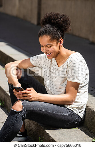 smiling young african american girl sitting outside looking at cellphone - csp75665018