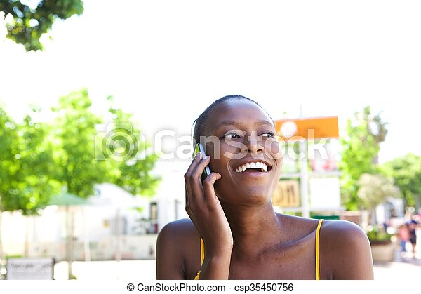 Smiling young african woman in the city talking on cellphone - csp35450756