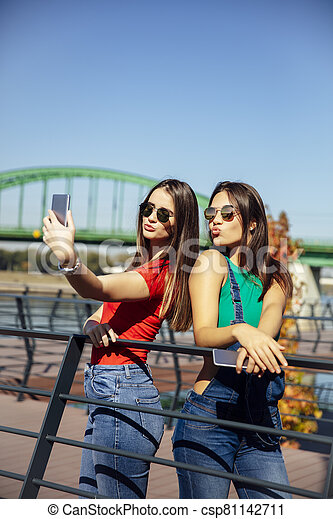 Smiling young best female friends taking selfie in the park - csp81142711