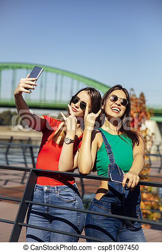 Smiling young best female friends taking selfie in the park - csp81097450