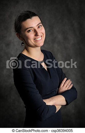 Smiling young brunette woman in black dress - csp36394005