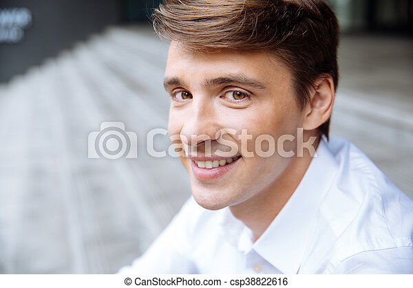 Smiling young businessman in white shirt sitting outdoors - csp38822616
