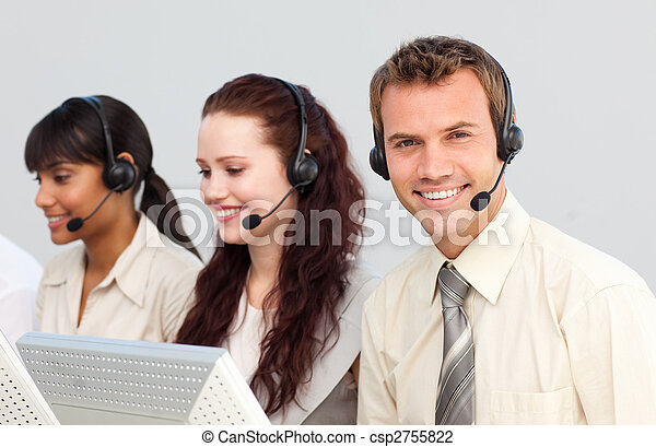 Smiling young businessman working in a call center - csp2755822
