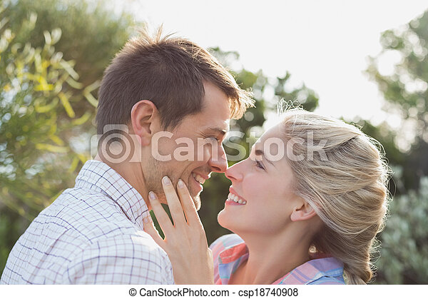 Smiling young couple looking at each other in park - csp18740908