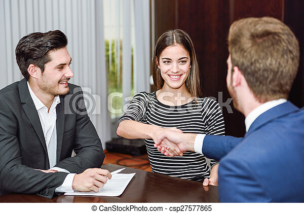 Smiling young couple shaking hands with an insurance agent - csp27577865