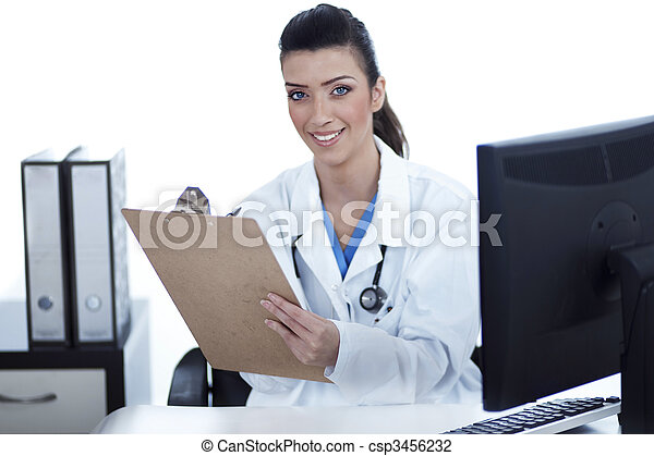 Smiling young doctor with clipboard in hand looking at the camera - csp3456232
