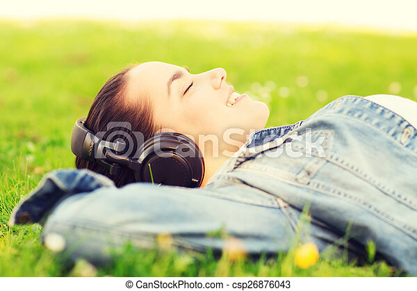 smiling young girl in headphones lying on grass - csp26876043