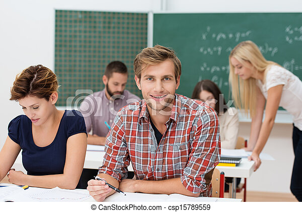 Smiling young man at college or university - csp15789559