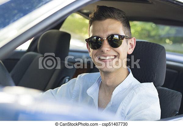 smiling young man in car - csp51407730