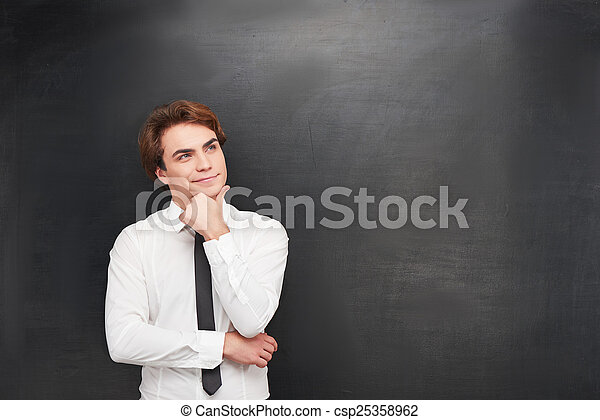 Smiling young man on chalkboard background - csp25358962
