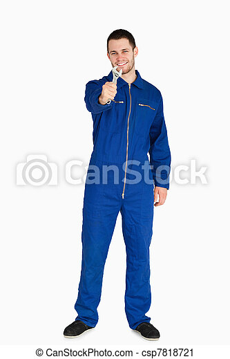 Smiling young mechanic in boiler suit presenting his wrench - csp7818721