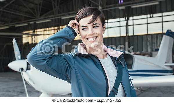 Smiling young pilot posing with a propeller plane - csp53127853