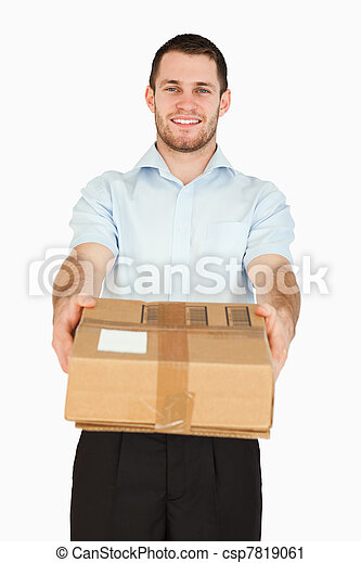 Smiling young post employee handing over parcel - csp7819061
