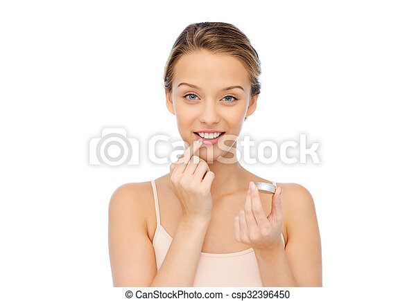 smiling young woman applying lip balm to her lips - csp32396450