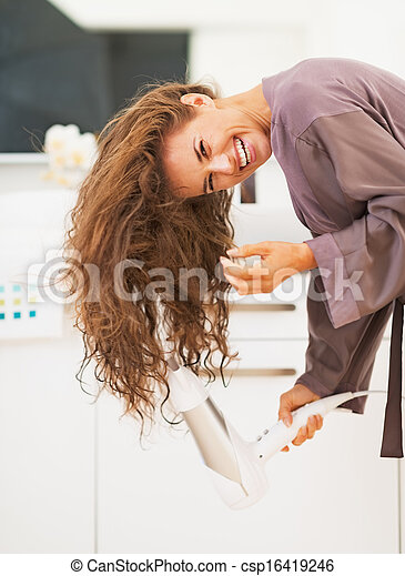 Smiling young woman blow drying hair in bathroom - csp16419246