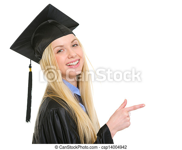 Smiling young woman in graduation gown pointing on copy space - csp14004942