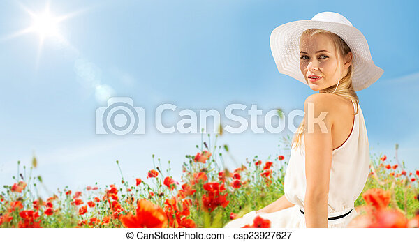 smiling young woman in straw hat on poppy field - csp23927627