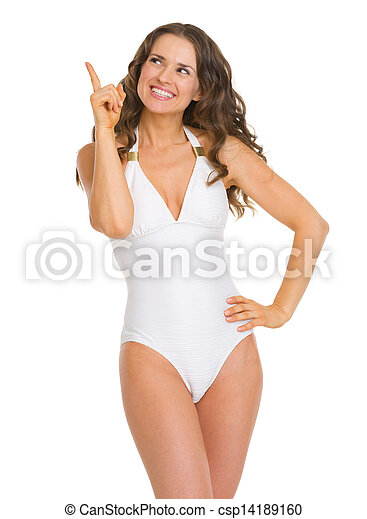 Smiling young woman in swimsuit pointing up on copy space - csp14189160