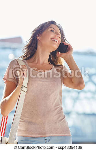 smiling young woman in the city with cellphone and bag - csp43394139