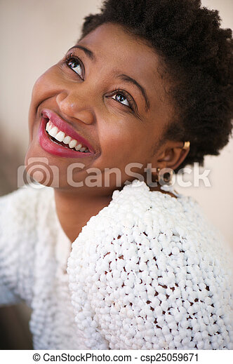 Smiling young woman looking up - csp25059671
