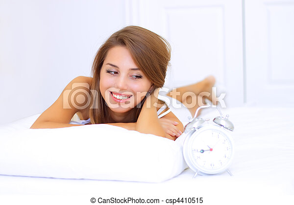 smiling young woman looks at the clock - csp4410515