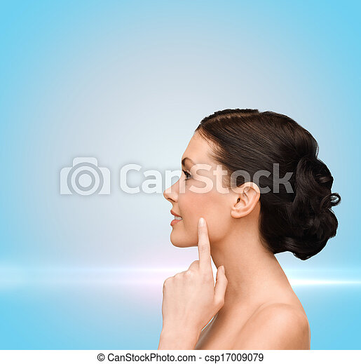 smiling young woman pointing to her cheek - csp17009079
