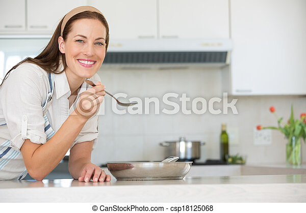 Smiling young woman preparing food in kitchen - csp18125068