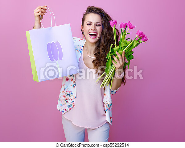 smiling young woman showing bouquet of flowers and shopping bag - csp55232514