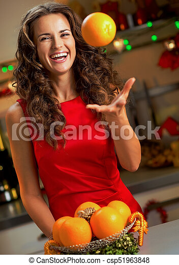 Smiling young woman throwing up orange in christmas ...