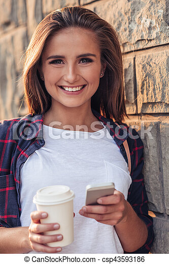 Smiling young woman using a cellphone in the city - csp43593186