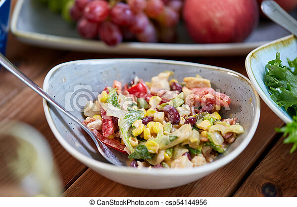 smoked chicken salad in bowl on wooden table - csp54144956