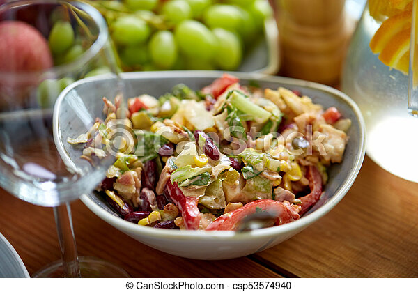 smoked chicken salad in bowl on wooden table - csp53574940