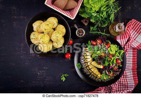 Smoked mackerel, boiled potatoes and fresh salad on dark background. Top view - csp71827478