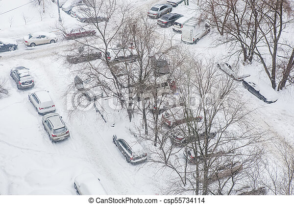 Snow-covered cars parked in the courtyard of a residential area - csp55734114