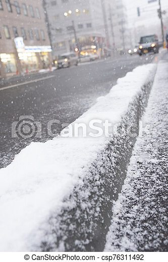 Snow covered sidewalk in Sapporo city - csp76311492