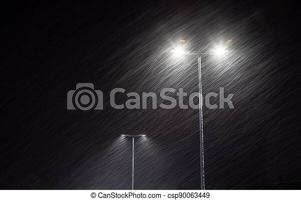 Snow falling on the background of a burning street lamp. - csp90063449