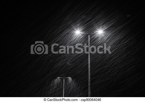 Snow falling on the background of a burning street lamp. - csp90064046